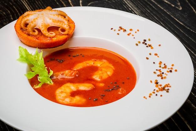 Ciotola di zuppa di pomodoro con gamberi con polpo al forno su una fetta di arancia su un fondo di legno nero...