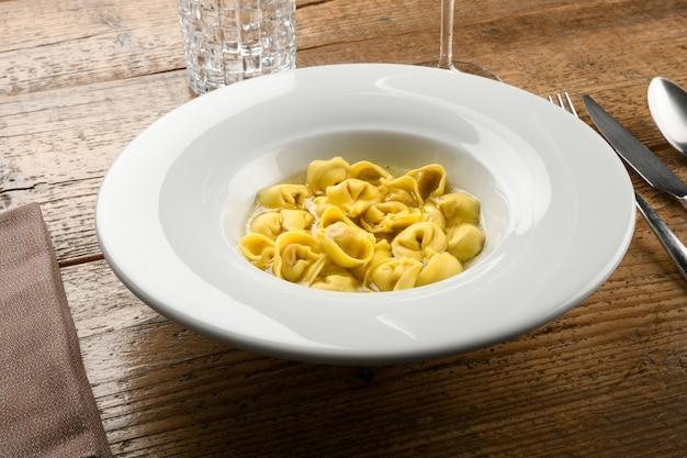 Ciotola di tortellini o cappelletti in brodo della regione emilia romagna d'italia servita in un elegante piatto bianco a tavola