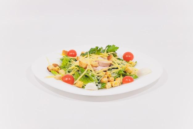 Ciotola di caesar salad tradizionale con pollo e pancetta isolato su sfondo bianco.