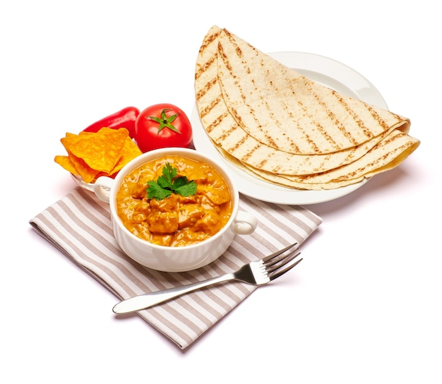 Ciotola di pollo al curry tradizionale e nachos isolati