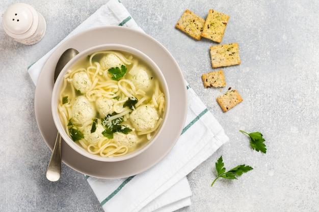 Ciotola di zuppa italiana tradizionale con polpette di carne di pollo e pasta d'uovo, parmigiano, prezzemolo sulla parete del tavolo grigio. cucina italiana tradizionale. vista dall'alto.