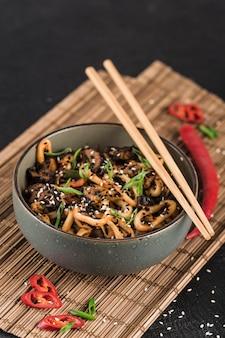 Una ciotola di noodles udon con anelli di calamari e funghi con bacchette e peperoncino su una superficie scura