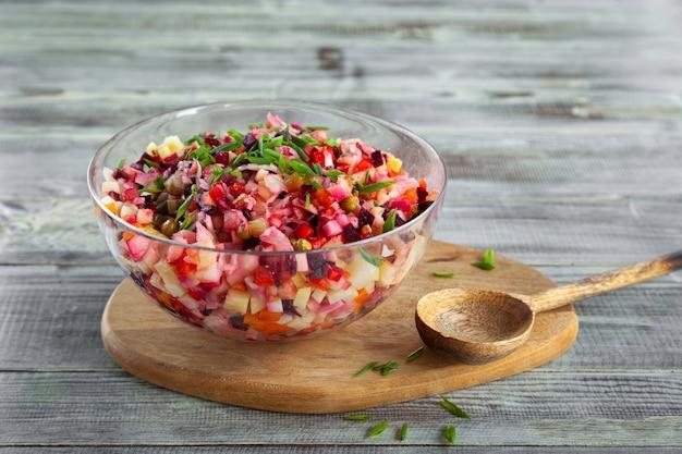 Ciotola di insalata tradizionale di barbabietola vinaigrette, tavola di legno, cucchiaio