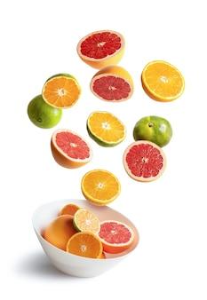 Ciotola con arance assortite e mandarini in volo, isolato su sfondo bianco
