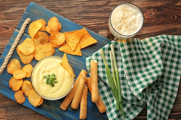 Ciotola con salsa di formaggio alla birra e patatine su tavola di legno
