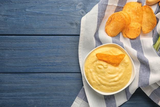 Ciotola con salsa di formaggio alla birra e nacho su fondo di legno