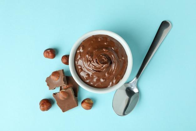 Ciotola con pasta di cioccolato, noci, cioccolato e cucchiaio su sfondo blu