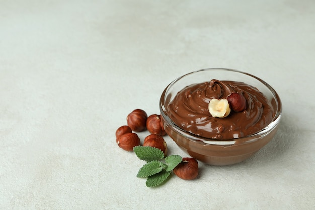 Ciotola con pasta di cioccolato, noci e menta su sfondo bianco strutturato