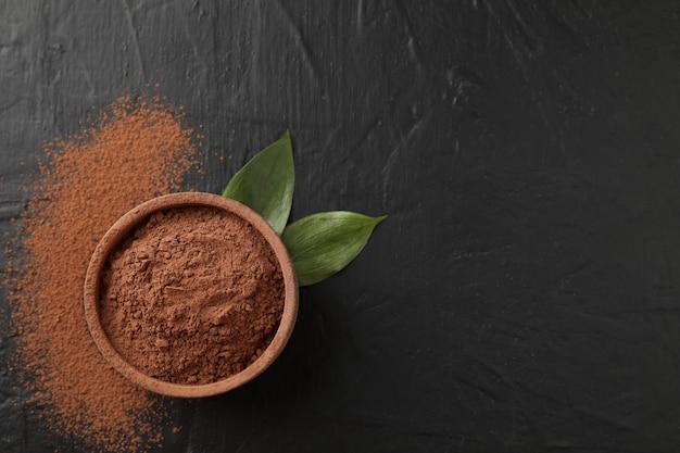 Ciotola con cacao in polvere e foglie sul nero, spazio per testo