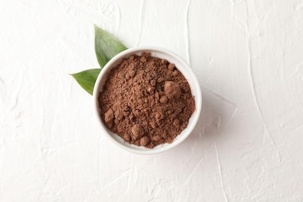 Ciotola con cacao in polvere e foglie su bianco, spazio per testo