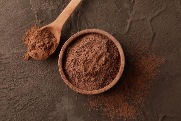 Lanci con cacao in polvere e cucchiaio su marrone, primo piano