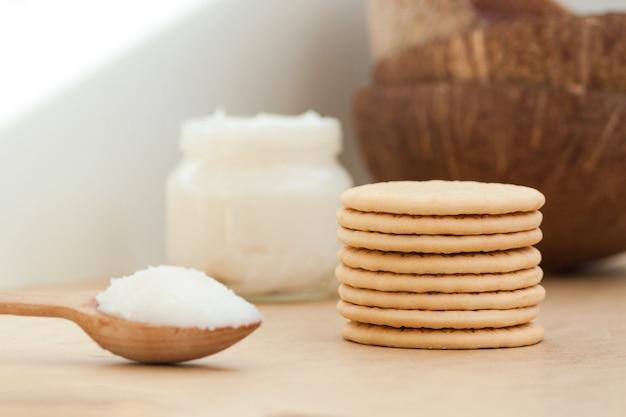Ciotola con olio di cocco e biscotti su fondo di legno