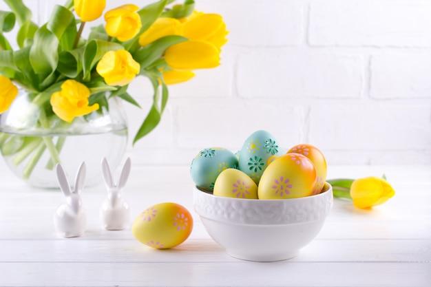Lanci con le uova di pasqua variopinte, decorazione di pasqua della molla sulla tavola di legno bianca con il mazzo dei fiori gialli del tulipano in vaso di vetro su fondo bianco. decorazione interna di pasqua