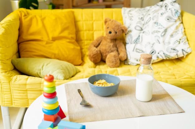 Ciotola con fiocchi di mais, bottiglia di acqua e cucchiaio sul tovagliolo di lino preparato per un bambino con orsacchiotto e cuscini sul lettino giallo