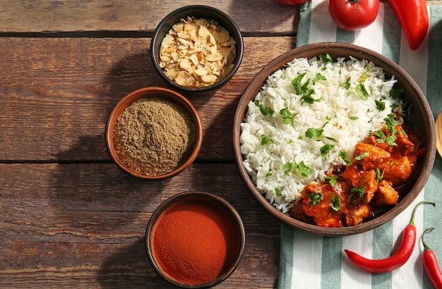 Ciotola con delizioso pollo tikka masala, riso e spezie su tavola di legno
