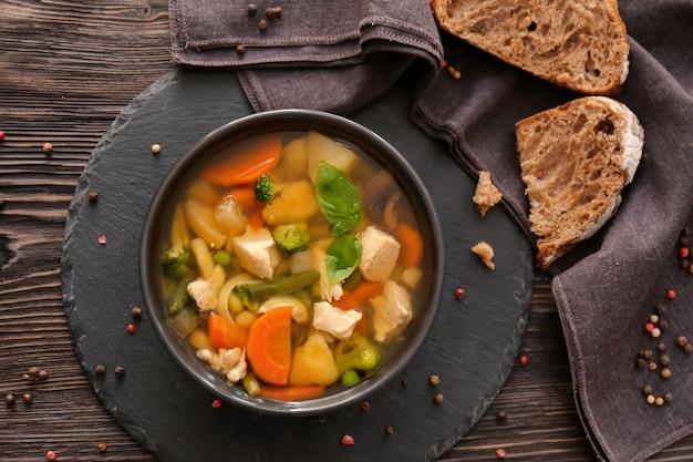 Ciotola con deliziosa zuppa di tacchino su piatto di ardesia