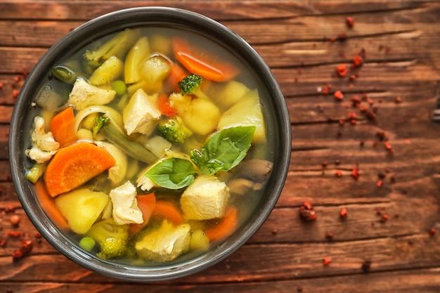 Ciotola con deliziosa zuppa di tacchino su legno Foto Premium