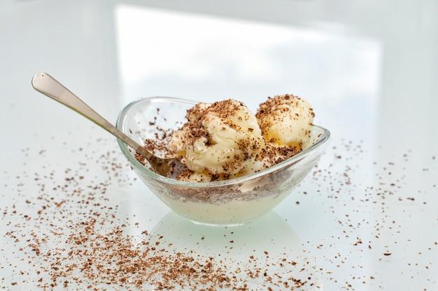 Ciotola con delizioso gelato alla vaniglia cosparso di gocce di cioccolato con un cucchiaio sul tavolo