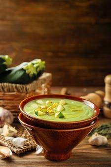 Ciotola con deliziosa zuppa di zucchine sul tavolo di legno