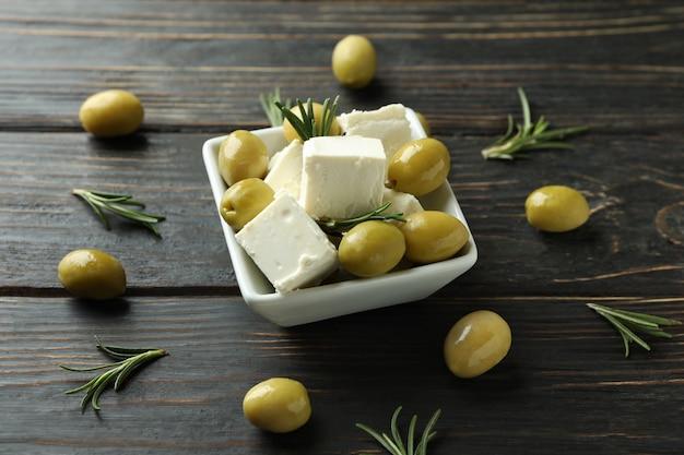 Ciotola con formaggio feta, olive e rosmarino su una superficie di legno
