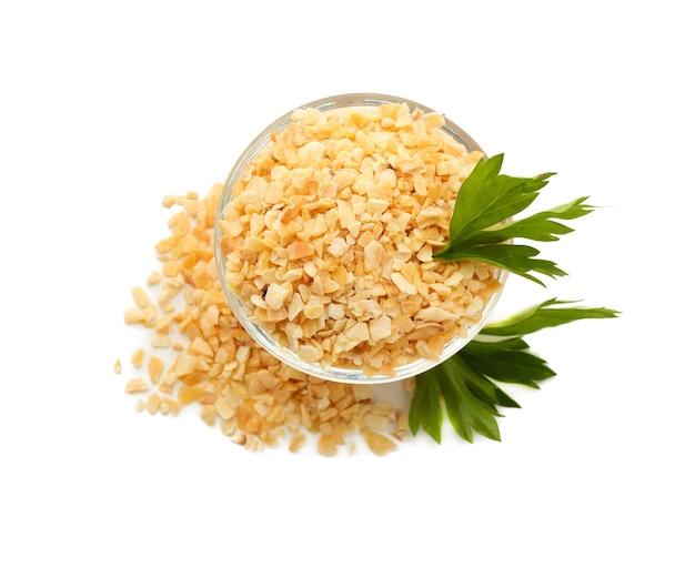 Ciotola con aglio secco granulato sulla superficie bianca