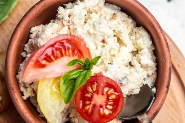 Ciotola con ricotta fatta in casa, pomodorini e basilico su una tavola di legno. tendenza alimentare sana.
