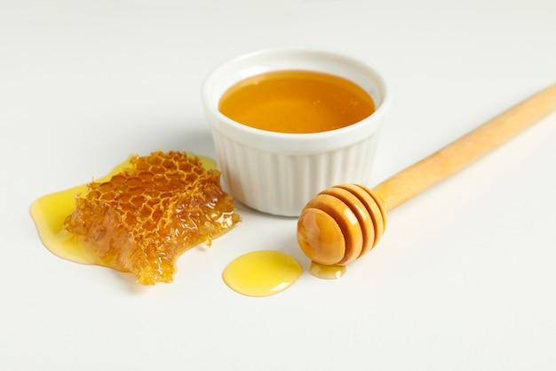 Ciotola con miele, mestolo e favi su sfondo bianco