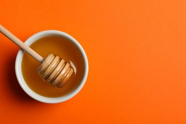 Ciotola con miele e mestolo sull'arancia