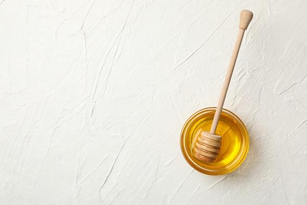 Ciotola con miele e mestolo su sfondo bianco, vista dall'alto