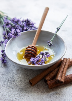 Ciotola con miele e fiori di lavanda fresca su uno sfondo di cemento