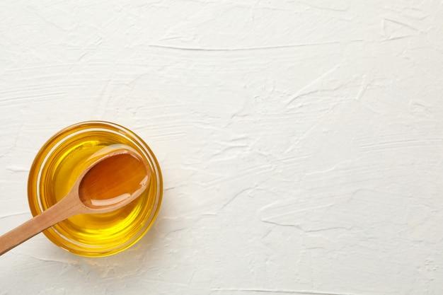 Ciotola con miele e cucchiaio su sfondo bianco, vista dall'alto