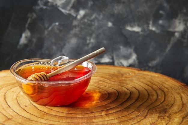 Ciotola con miele e un bastone di legno su legno