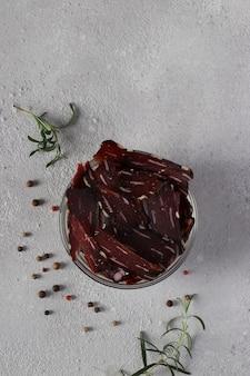 Ciotola con carne a scatti, peperoni e rosmarino su sfondo grigio chiaro. formato verticale. vista dall'alto