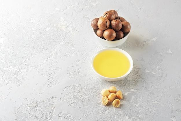 Ciotola con olio di macadamia sul tavolo di cemento grigio.