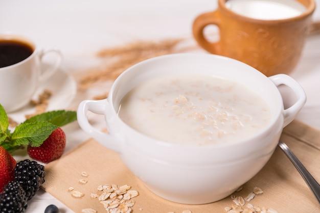 Ciotola con porridge di farina d'avena contro il tavolo della colazione in vista ravvicinata