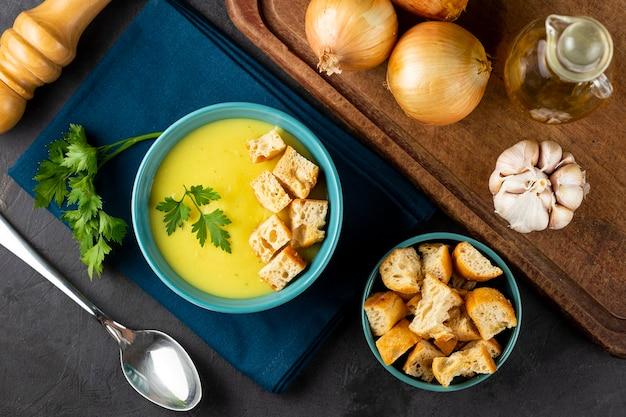 Ciotola con zuppa di cipolle e crostini sul tavolo.
