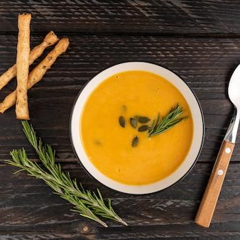 Una ciotola con zuppa di crema di zucca con grissini grossini e formaggio su fondo di legno scuro.