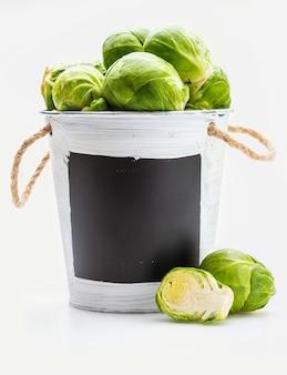 Ciotola con cavoletti di bruxelles crudi, freschi, interi e tagliati (cavoli - brassica oleracea). copia spazio. isolato su bianco