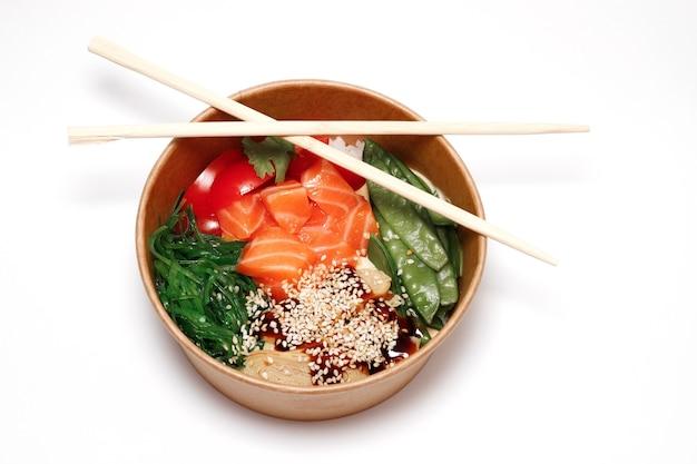 Ciotola con salmone, frittata e chuka in piatti di carta usa e getta con bacchette cinesi consegna cibo