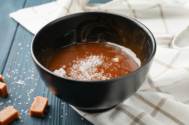 Lanci con caramello e le caramelle salati su spazio di legno, fine in su