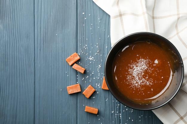Ciotola con caramello salato e caramelle su spazio in legno, spazio per il testo