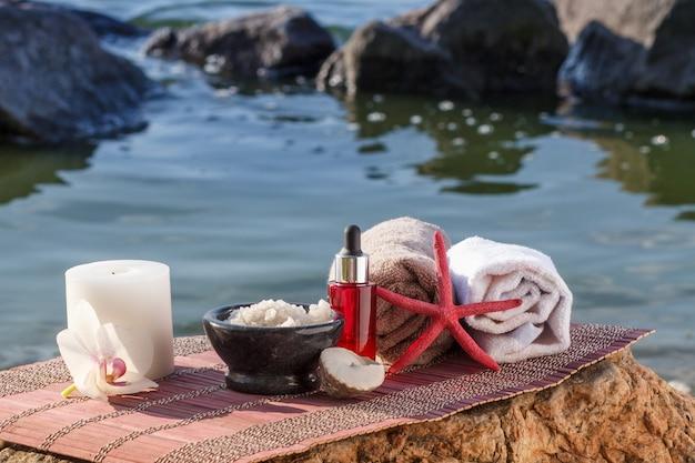 Ciotola con sale marino, bottiglie con olio aromatico, candela, fiore di orchidea, conchiglia, stella marina e asciugamani con panno di bambù su pietre. prodotti spa su sfondo naturale