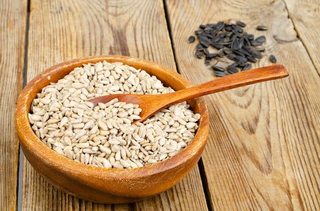 Ciotola con semi di girasole su una superficie di legno
