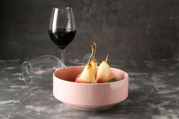 Ciotola con pere dolci stufate nel vino rosso sul tavolo