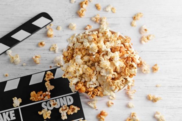 Ciotola con gustosi popcorn al caramello e valvola di film su legno