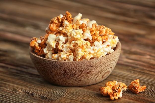 Ciotola con gustosi popcorn al caramello sulla tavola di legno