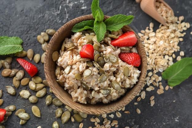 Ciotola con gustosa farina d'avena, fragola e semi di zucca su sfondo grigio strutturato