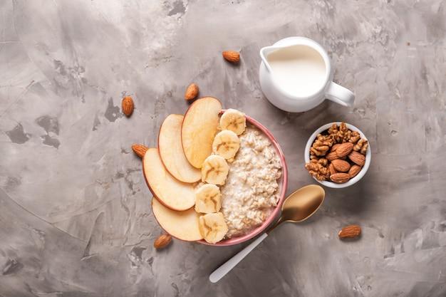 Ciotola con gustosa farina d'avena dolce, noci e latte su grunge