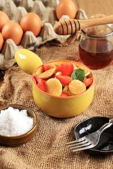 Ciotola con piccoli cereali per pancake con fragole e foglie di menta su uno sfondo bianco. e piatto di legno. cibo alla moda. mini pancake ai cereali. orientamento verticale