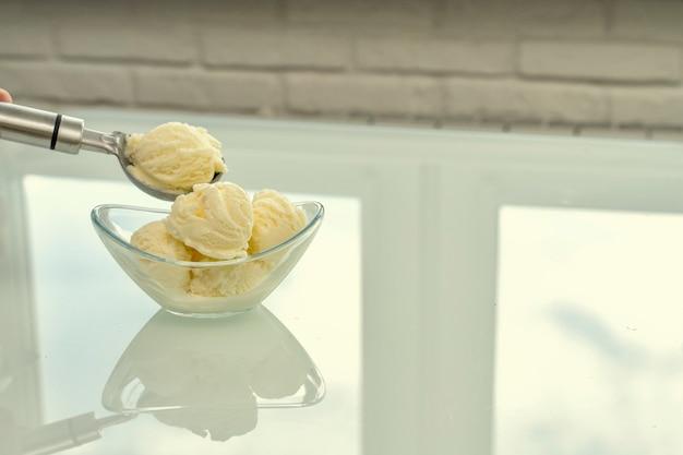 Una ciotola con gelato alla vaniglia si trova su un tavolo luminoso riflettente